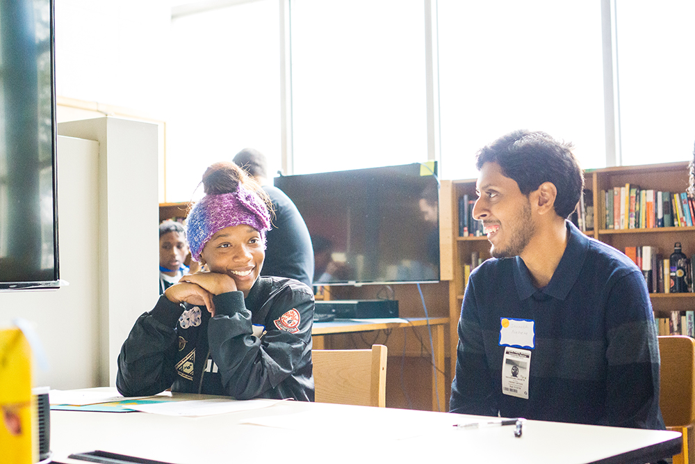 A buildOn student and student from Michigan State smile and laugh as they get to know each other through an Icebreaker activity.