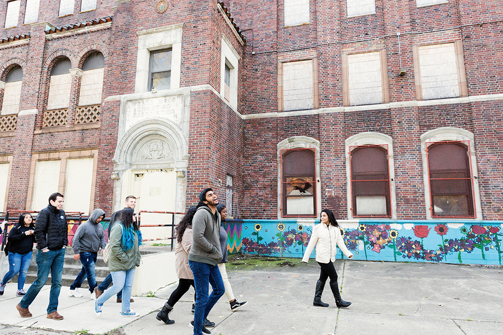 Students from MSU and buildOn walk past an abandoned building that has been boarded up in Detroit.