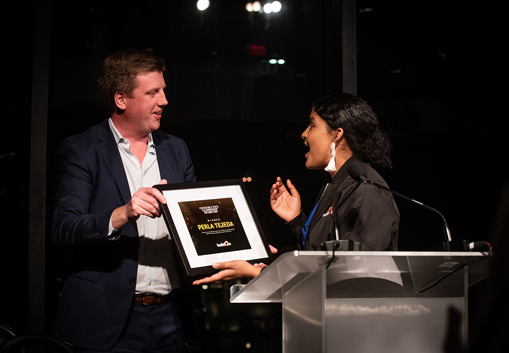Stephen Coyle, a buildOn Board Member in Boston, surprises Perla, a buildOn student, with the Constructive Leadership for her outstanding leadership and service in Boston. Perla smiles and looks surprised as Stephen hold a plaque with her name.
