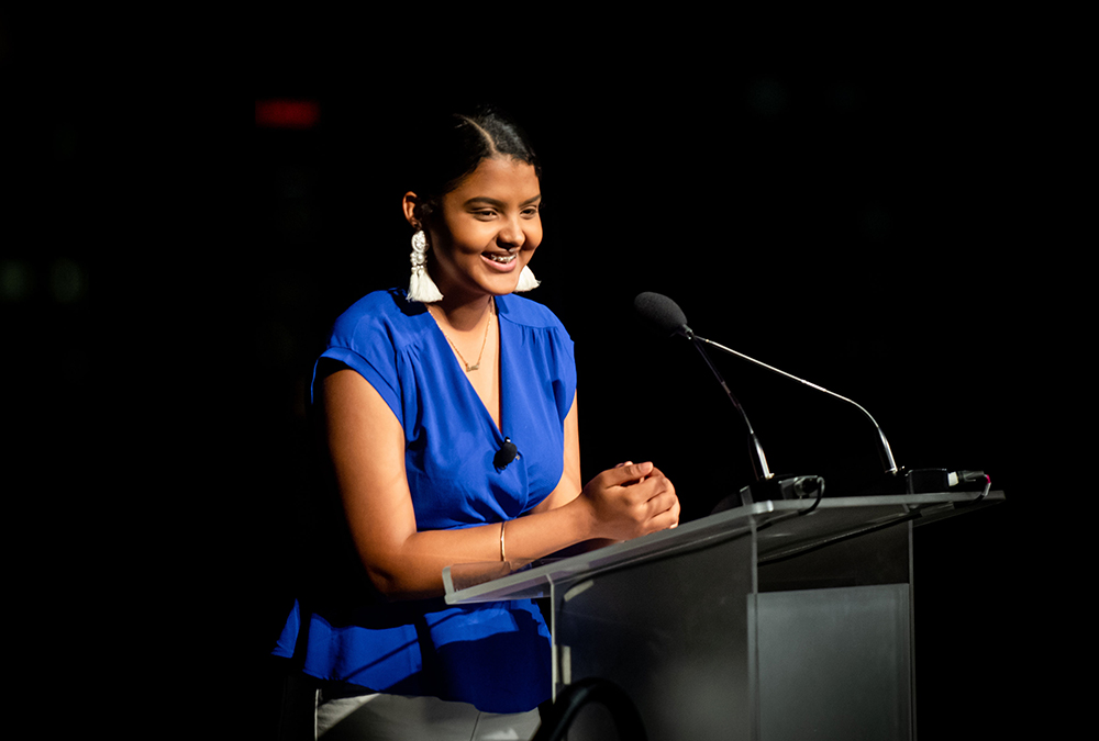 Perla, a buildOn student in Bosotn, smiles at the podium while giving her speech at the Boston Dinner.
