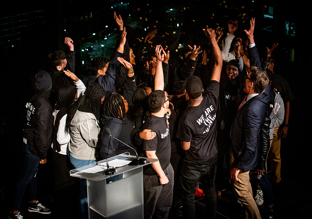 Students and buildOn staff cheer on the stage with their hands in the center at the end of the celebration.