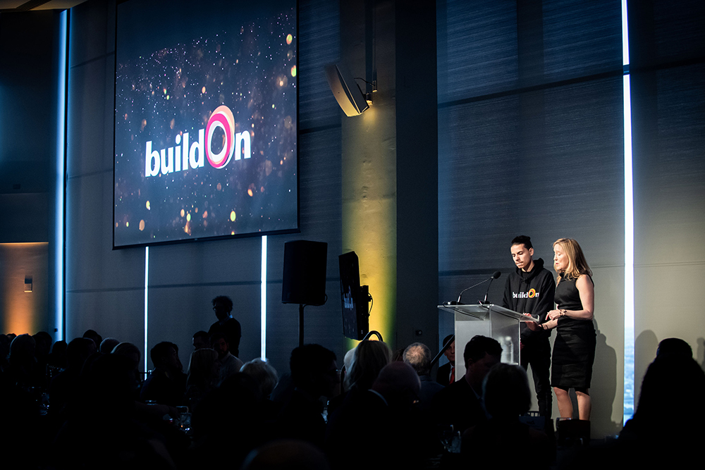 A buildOn student and buildOn Boston Board member stand at the podium of a large stage, kicking off the event.