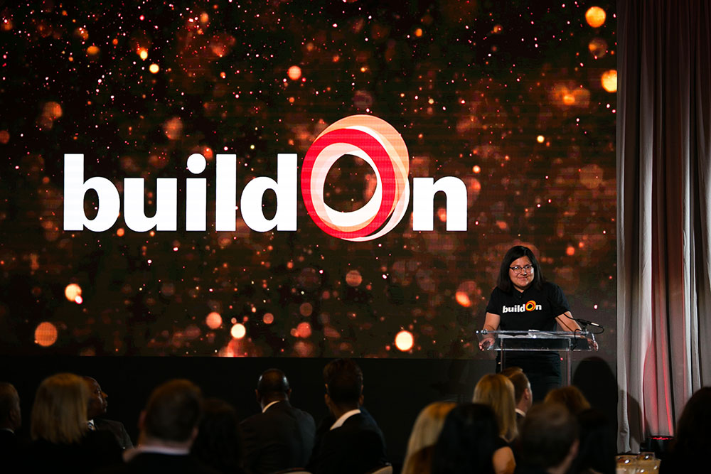 Cris, a buildOn student from Gage Park, speaks on stage in front of a large glittering buildOn logo.