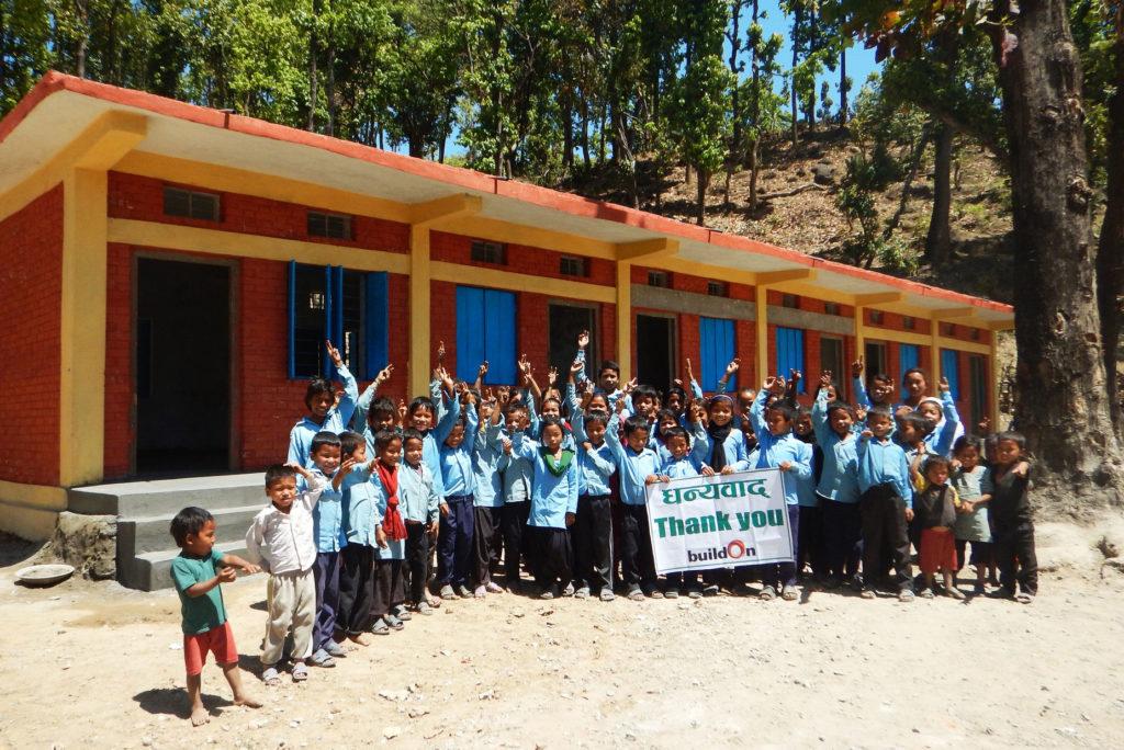 Children celebrate outside of their new school in Bhategada Village
