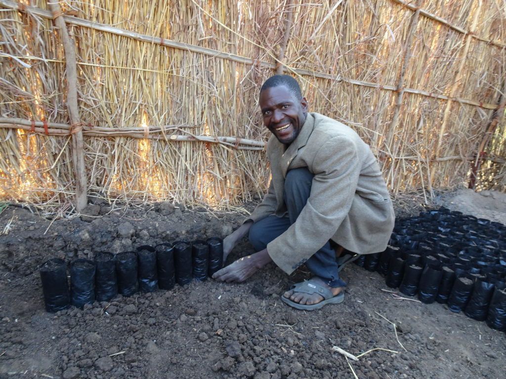 An ALP student crouching down beside rows of recently sowed seeds.