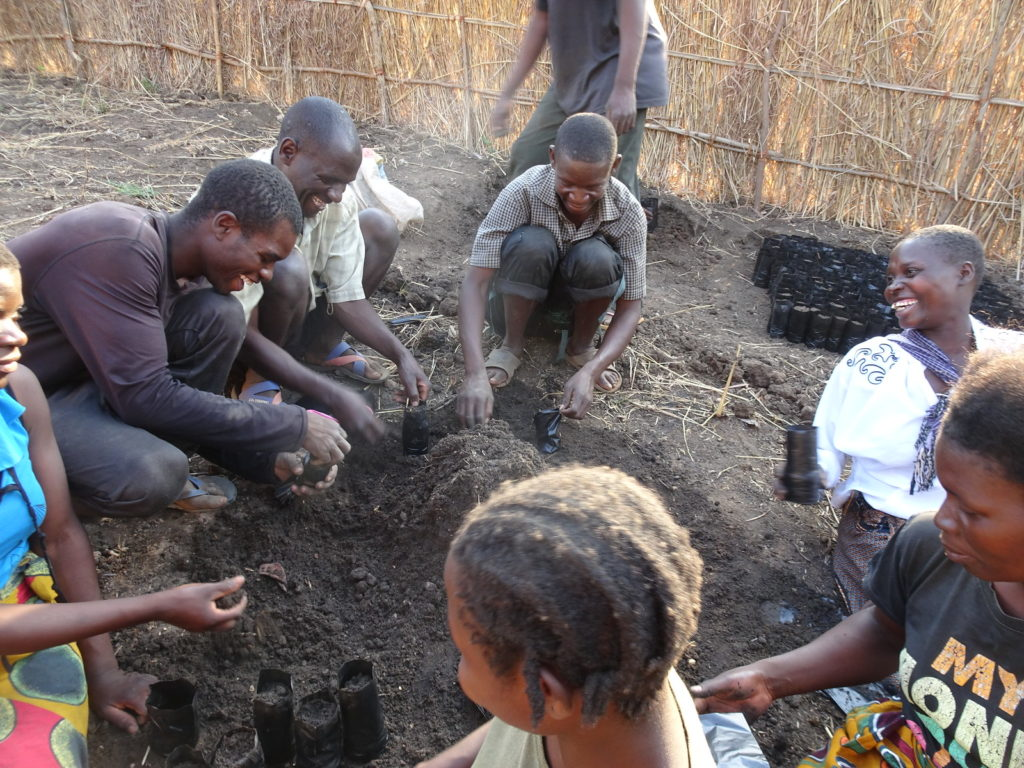 Learners from Chilumba, circled around a pile of soil, fill polythene tubes with soil as part of the seed sowing process