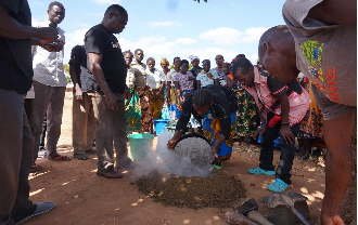Female community member empties bucket into pile, while buildOn staff stands above and community members circle around.