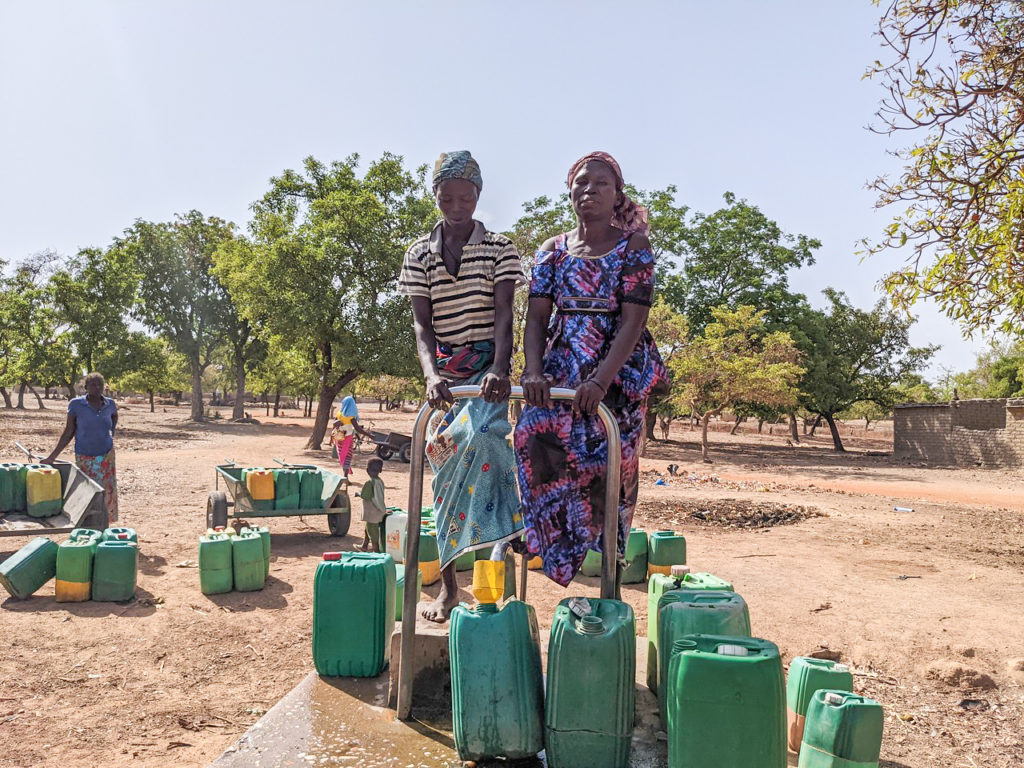 Nignan Kakoira from Sia, Burkina Faso, stands by other woman at the pump for the water well.