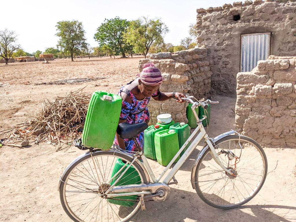 Nignan Kakoira from Sia, Burkina Faso, loads up her bike with water jugs to take to the well.