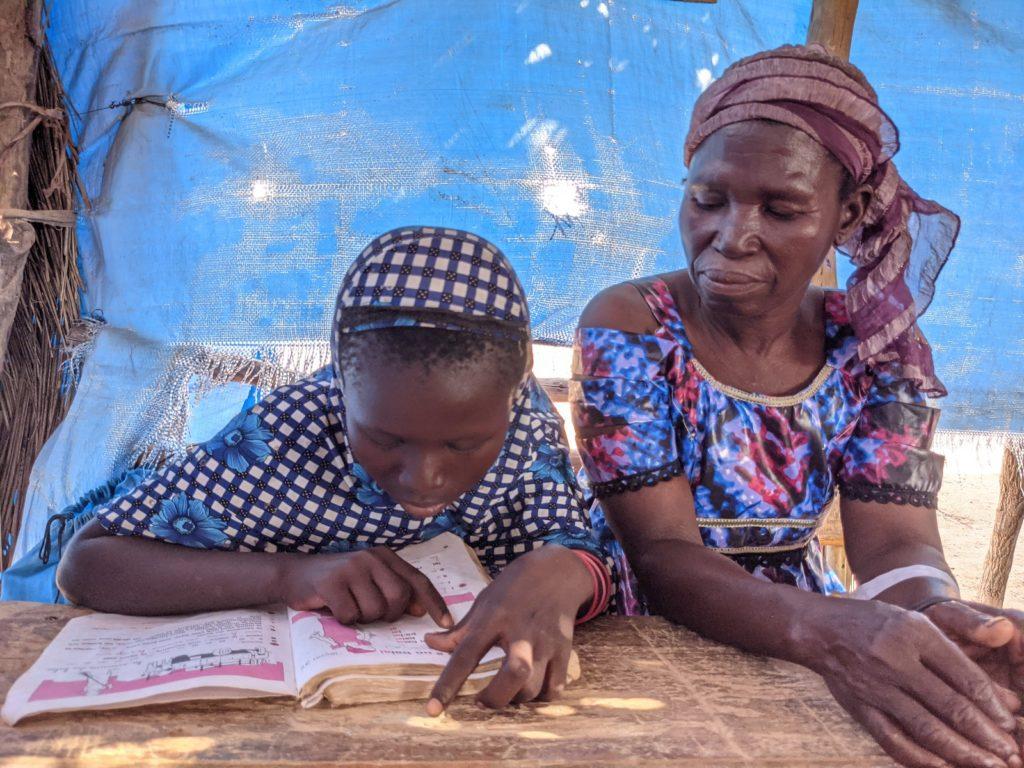 Nignan Kakoira from Sia, Burkina Faso, watches her granddaughter reading.