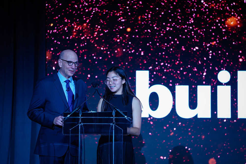 buildOn Chief Revenue Officer Marc Friedman and buildOn student Kimberley stand on stage welcoming everyone to the 2019 Bay Area Dinner as emcees.