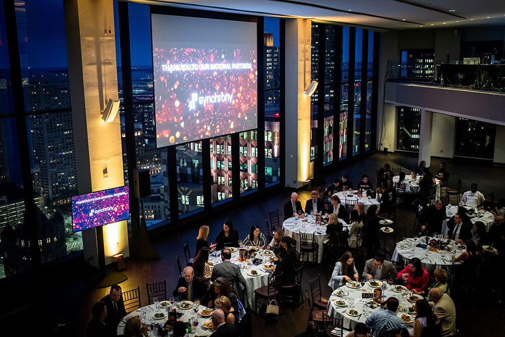 A view of tables, guests, and the skyline of Boston from the State Room location.