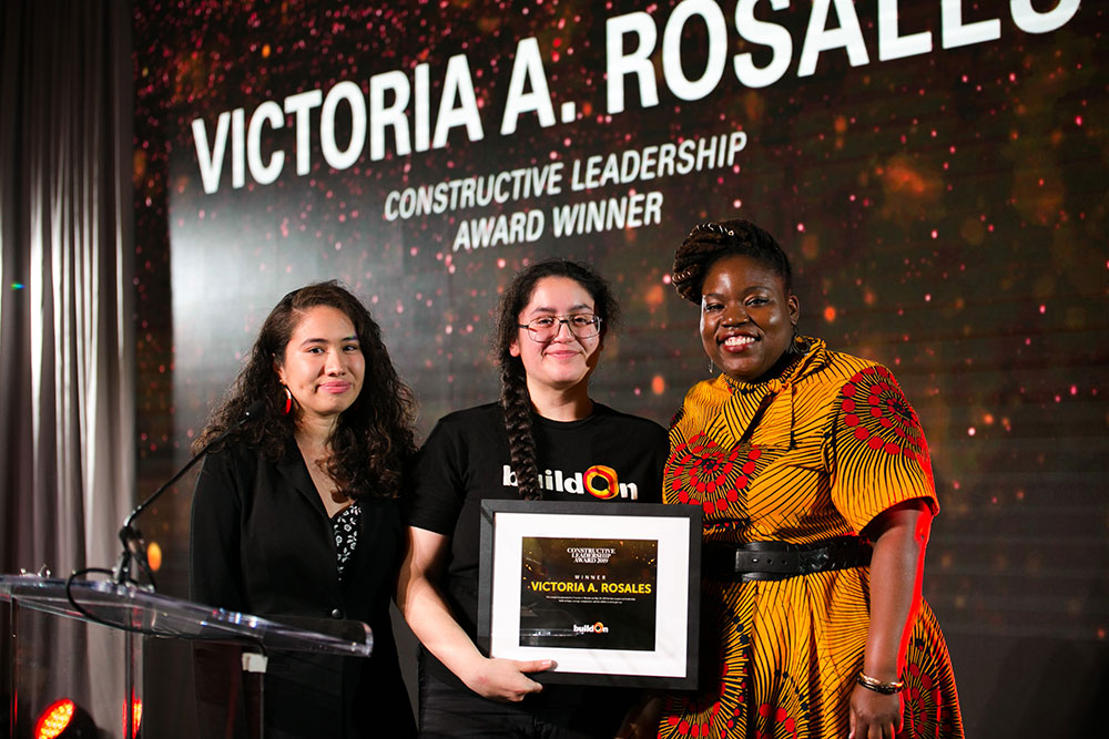 Victoria, a buildOn student from Chicago, stands on stage holding the Constructive Leadership Award. She is beaming and standing next to two buildOn staff from Chicago who are proud to see her win the award.