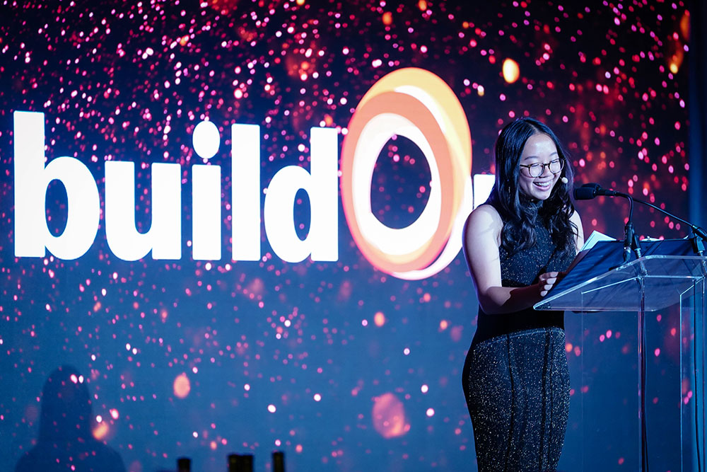 Crystal, a buildOn student from Oakland, stands on stage and shares her story of giving back and serving her community.