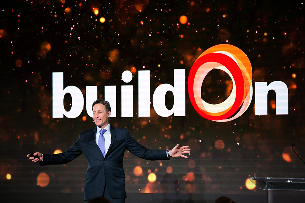 buildOn's founder speaks from the stage in front of a glittering buildOn logo.