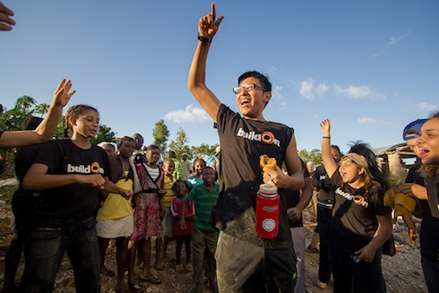 Marco Torres cheers on other buildOn students while breaking ground on a school in Lescaves, Haiti with the villagers in February.