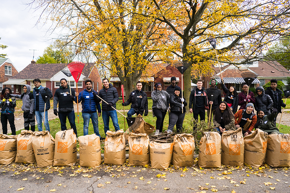Michigan State MBA students and buildOn students pose with rakes and full bags of leaves after raking leaves for elderly residents of Detroit.