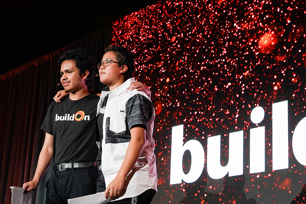 Siblings Francisco and Maria stand with arms over each other's shoulders after performing their spoken word poem at the 2019 Bay Area Dinner.