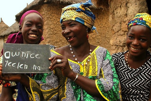 """Komba Dumbia, 58, stands with her granddaughters in Mali, holding a board that reads """"thank you for bringing the light."""""""